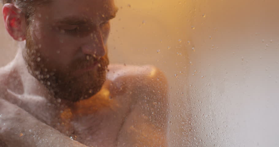 The close-up portrait of the depressed man taking the shower. The view through the glass bath shower. | Shutterstock HD Video #29767072