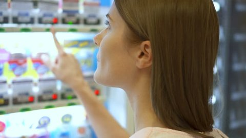 Beautiful hungry woman picking item out of vending machine in mall. Choosing unhealthy snacks being famished