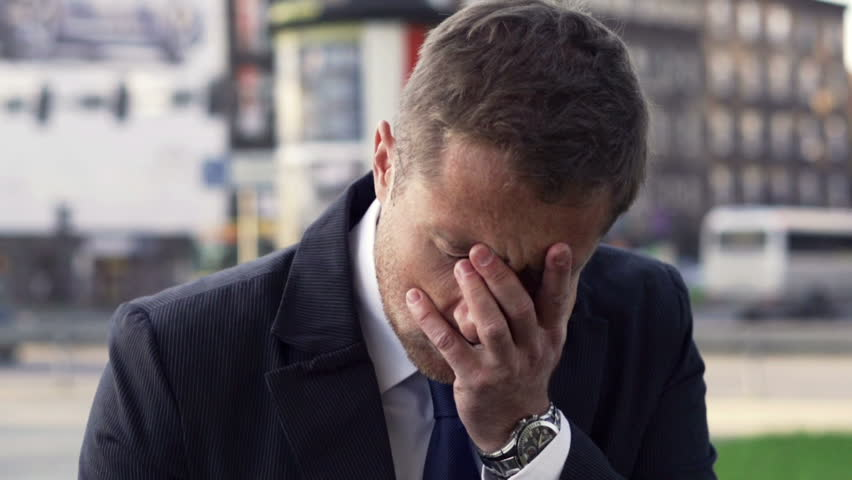Portrait of depressed businessman standing on the street, slow motion shot at 240fps