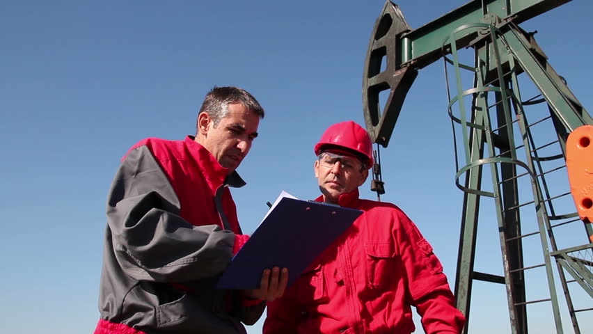 Oil Worker Meeting. Two oil workers talking on oil rig. HD1080p.
