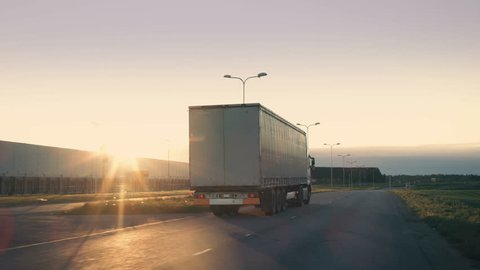 Follow-up Shot of a Semi-Truck with Cargo Trailer Moving on a Highway. White Truck Drives Through Industrial Warehouse Area on an Empty Road with Sun Shining in the Background. 4K UHD.