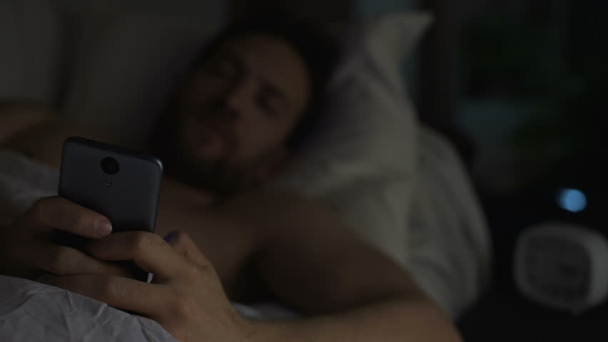 Young adult man can't sleep, yawning and browsing the net on cellphone, insomnia #29801992