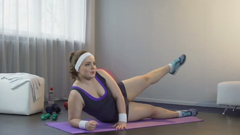 Tranquil girl getting moral pleasure from exercising and bringing body in order