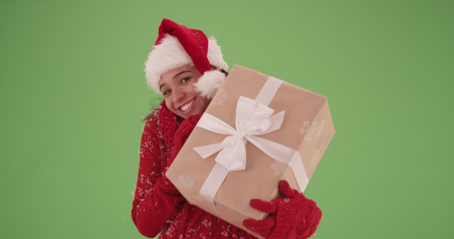 Happy Hispanic girl in a Christmas outfit holding a present on green screen. On green screen to be keyed or composited.