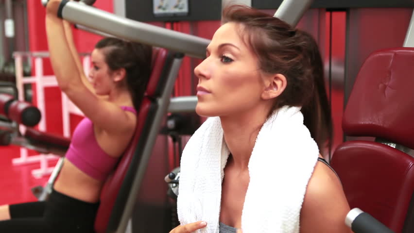 Woman wiping sweat away with white towel at weights machine