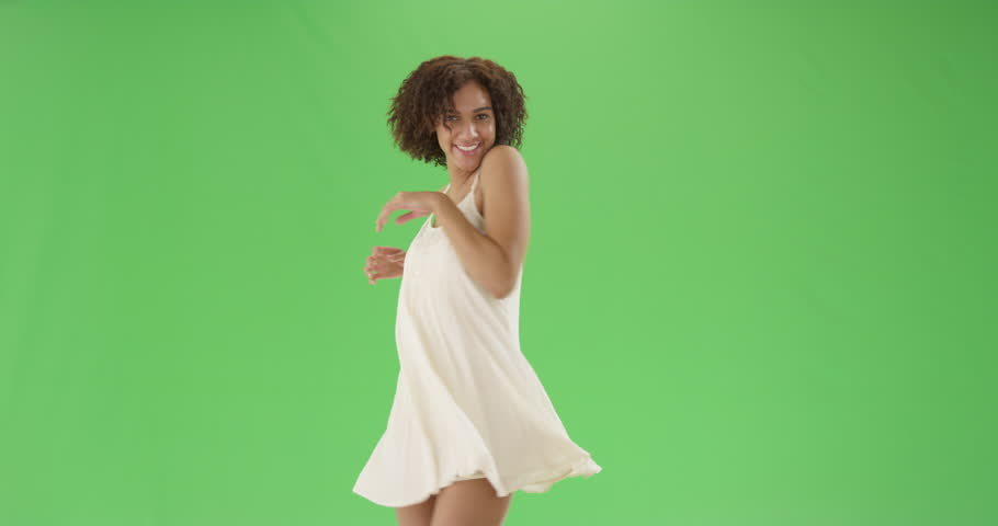 A young pretty African American woman twirls around in a sundress on green screen. On green screen to be keyed or composited.