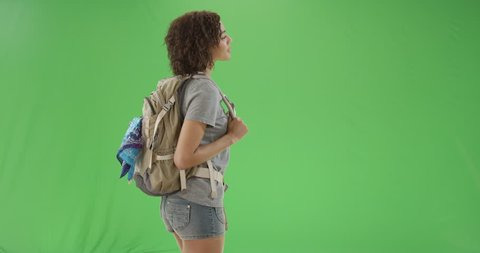 Young African American girl turns around looking cute and smiling at the camera on green screen. On green screen to be keyed or composited.