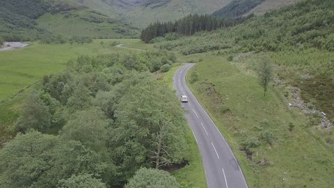 Aerial Shot of Car Driving Along Country Road in Scotland
