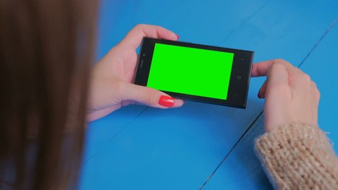 Woman using horizontal smartphone with green screen. Close up shot of woman's hands with mobile. Technology, chroma and internet concept