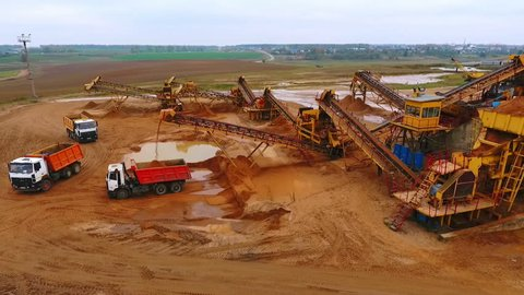 View from above mining conveyor working on sand mine. Mining conveyor pour sand in dumper truck. Mining equipment on industrial park
