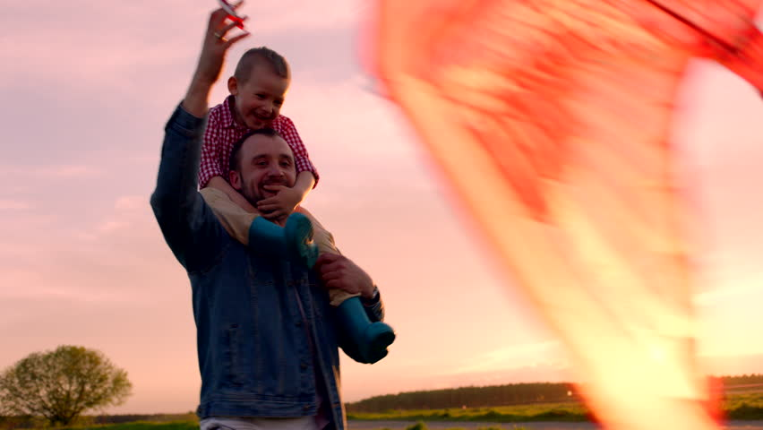 Little boy and his father playing flying kite in the park at sunset