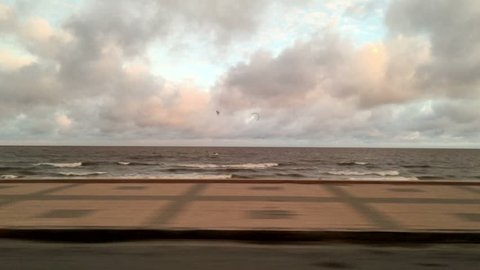 Passenger view of sear shore while on road trip vacations. Driving by the side of the beach during sunset time