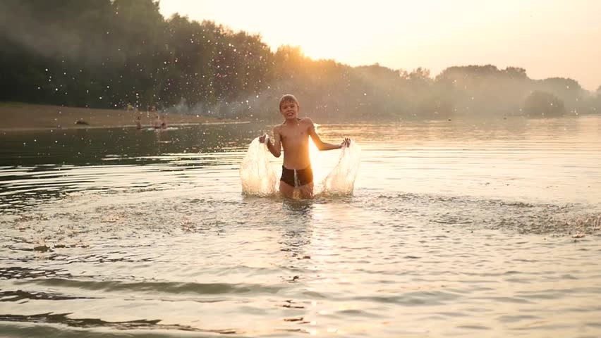 A child playing in the sea, creating a splash of water. Fun and games in the fresh air. Sunset time