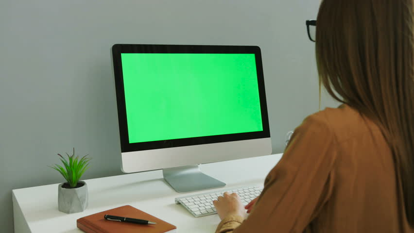 portrait of young woman in the glasses and casual shirt working on the computer with green