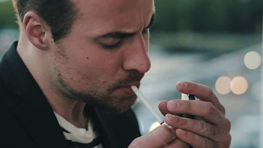 Handsome man takes a cigarette and light it up. Tired man smokes a cigarette