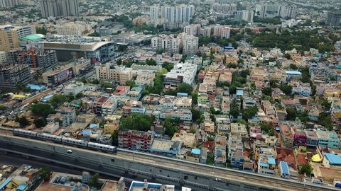 Aerial profile view of train over a busy metro city entering the Train station in India