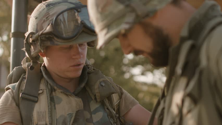 American soldier helps another to pack equipment on the military campaign