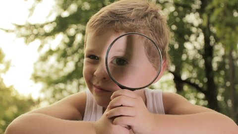 Little boy exploring nature by magnifier.