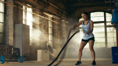 Athletic Female Actively in a Gym Exercises with Battle Ropes During Her Cross Fitness Workout/ High-Intensity Interval Training. She's Muscular and Sweaty, Gym is in Deserted Factory.