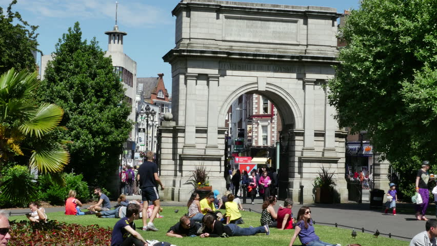 DUBLIN, COUNTY DUBLIN, IRELAND - JUNE 15, 2015: People relax on St. Stephen's Green by the Fusiliers' Arch that was erected to honor Dublin Fusilier who fought in the Second Boer War.