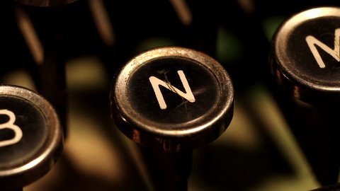 "A male finger presses the letter ""N"" key on an old typewriter."