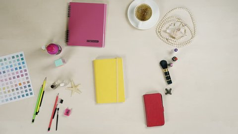 Woman's life, top view. Diary, cosmetics and jewelry on table, stop motion video. Top view of table with female accessorize, stop motion effect