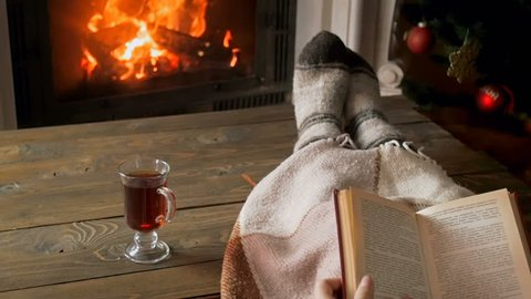 Slow motion footage of young woman reading book and drinking tea by the fireplace