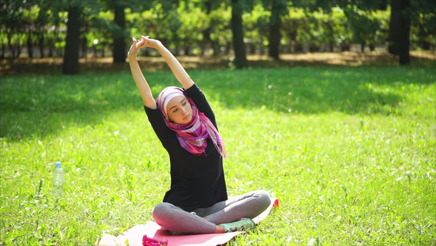 A young Muslim woman in a scarf, called a burqa, does stretching the back muscles, the lady is in the summer park and is doing sports