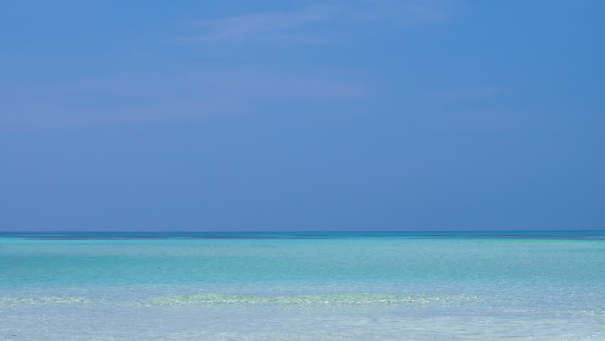 Tropical sandy beach with calm waves on sandbank. Maldivian destination with nobody