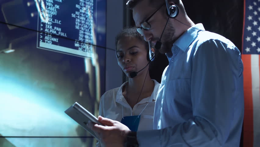 Side view of black woman and white man communicating in Moon mission control center. American flag on background.   Shutterstock HD Video #30005182