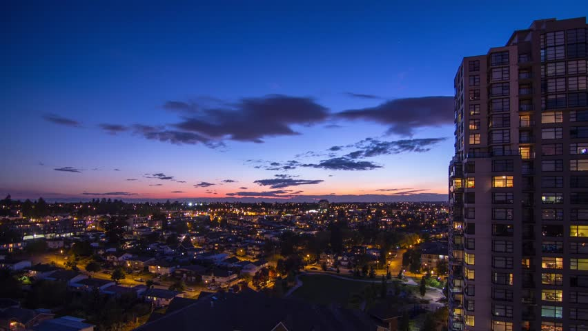 Time Lapse Lighten Up the city in a Residential Area with Houses and Apartment. Night sky changing from Clouds to clear starry night. Shot in 4k RAW photo sequence.