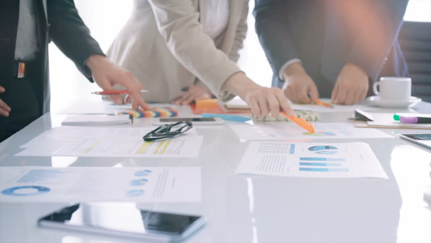 Business professionals holding a meeting. They are discussing ideas for the economic development of their company over financial charts and data.    Shutterstock HD Video #30032731