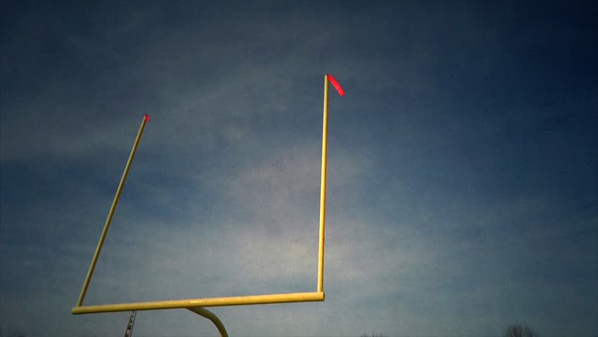 Football Goal Post - Time-lapse - A time-lapse of the football field goal post. The wind is blowing the flags as the clouds roll by.
