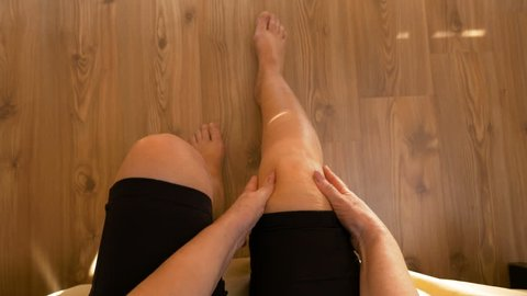 Point of view of woman sitting on bed and massaging both knees having joint ache