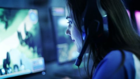 Professional Girl Gamer Plays in MMORPG/ Strategy Video Game on Her Computer. She's Participating in Online Cyber Games Tournament, or in Internet Cafe. She Wears Gaming Headphones. 4K UHD.