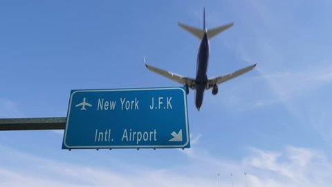 new york airport sign airplane passing overhead