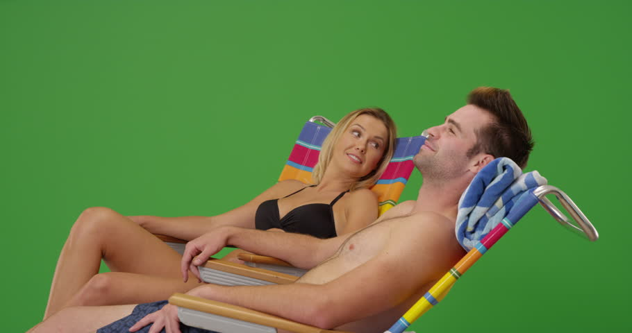 Cheerful white millennial couple sitting together by the beach on a nice warm day on green screen. On green screen to be keyed or composited.