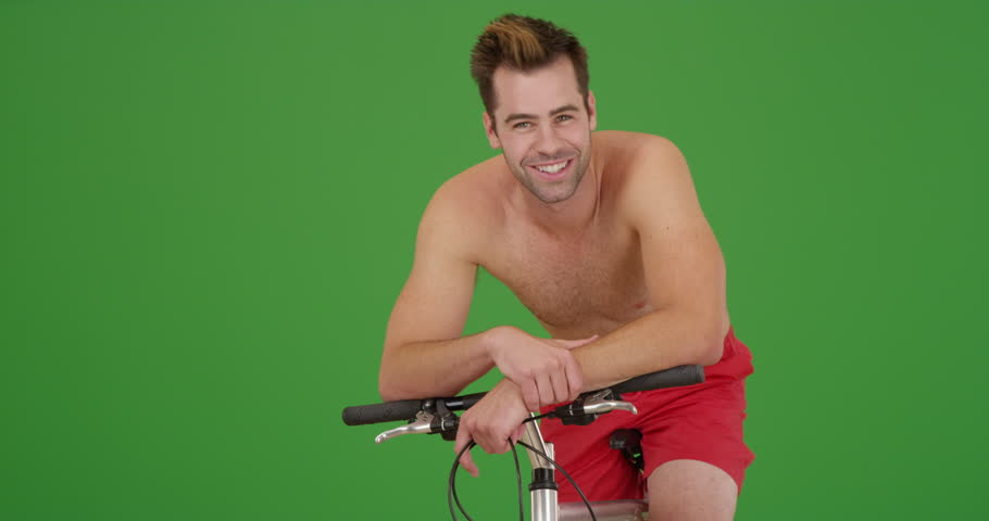 Young hot millennial sitting on bike smiling at camera on green screen. On green screen to be keyed or composited.