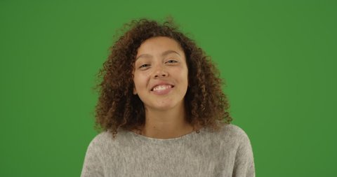 Happy laughing mixed-race millennial woman talking over video chat conference call on green screen. On green screen to be keyed or composited.