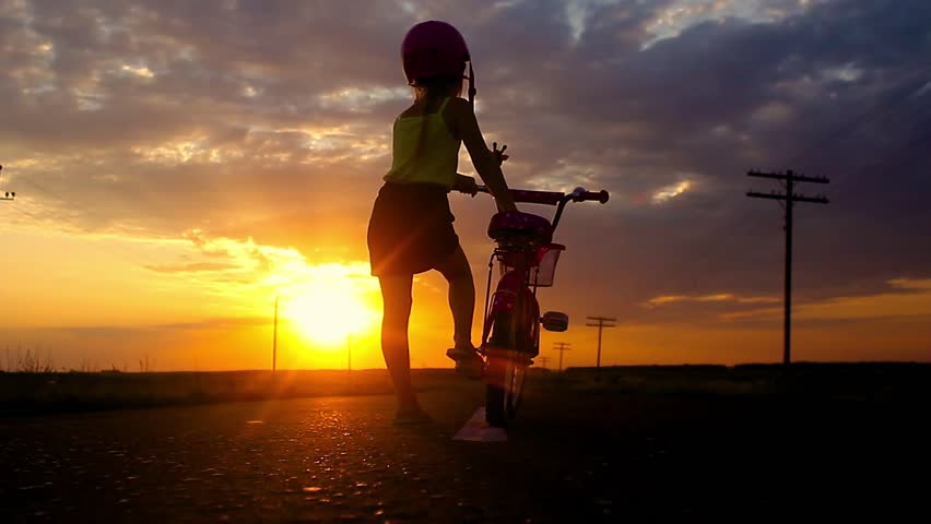 Little girl having fun riding bike at sunset, active family sport, active kids sport, Silhouette a kid at the sunset, Moments of family happiness. Orange-blue sky background. | Shutterstock HD Video #30088972