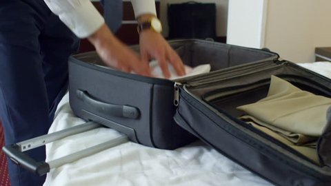 Tilt up of businessman packing his suitcase and putting clothes into it on bed in hotel room