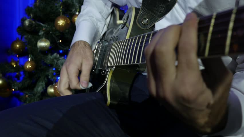 Christmas concert guitarist in white shirt playing guitar. Bright stage lights flashing, Slow Motion Effect.