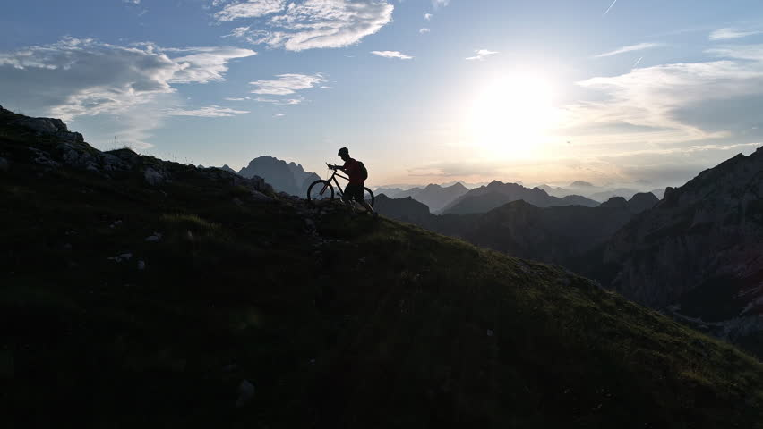 Aerial - Young man pushing his mountain bike up the steep hill at sunset | Shutterstock HD Video #30127111