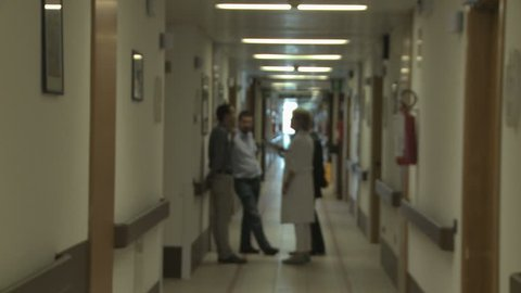 Hospice Hallway with female doctor talking to patient's relatives
