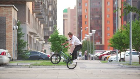 BMX freestyle on the city street. BMX flatland tricks. Hipster on the BMX bike.
