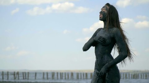 A slender girl in curative mud from the estuary covers her nakedness and looks into the distance