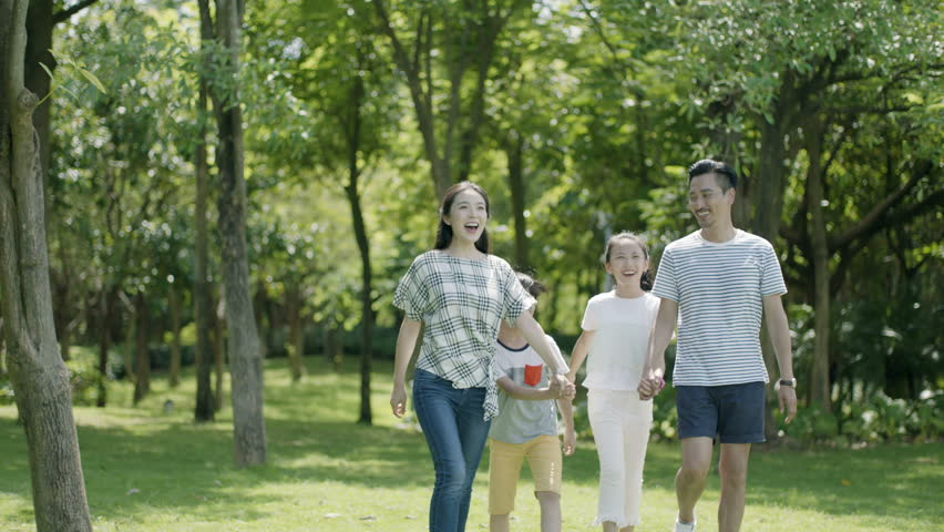 asian family of 4 walking & laughing in park in sunny summer in slow motion