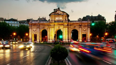 Madrid, Spain. Night view of The Puerta de Alcala at sunset in Madrid, Spain - a monument in the Independence Square. Motion blurred cars and buses, illumination and lights, violet sky. Time-lapse
