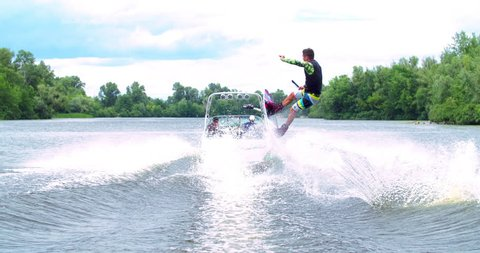 Wakeboarder doing tricks 4k wakeboarding slow-motion video. Man rides behind boat and jumps somersault flip on waves. Water extreme sport.