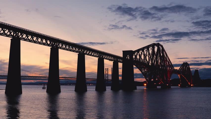 EDINBURGH, SCOTLAND - 26 August 2017: Establishing Shot, Silhouette of The Forth Bridge at Sunset with Train Crossing